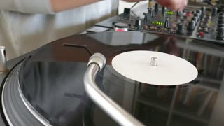 A DJ mixing music on an audio mixer and changes the vinyl...