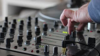 A DJ mixing music on an audio mixer and scratching on a vinyl...
