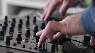 A DJ mixing music on an audio mixer and scratching on a vinyl