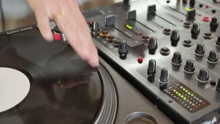 A DJ scratching on the vinyl and mixes music...