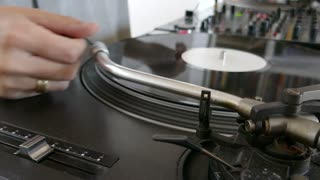 A DJ scratching on the vinyl and practicing music mixing...