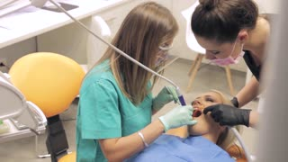 A female dentist and her assistant working on a patients teeth...