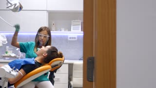 A moving shot in a dentists office, a young female dentist examining and working on the patients teeth, the shot is moving from left to right, the patient turns into camera and smiles...