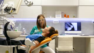 A moving shot in a dentists office, a young female dentist examining and working on the patients teeth...