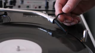 A moving shot of a person putting the needle on a rotating vinyl and starts to mix music on an audio mixer
