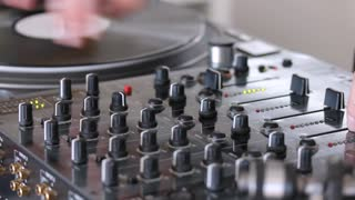 A moving shot of an audio mixer and person mixing some music on it...