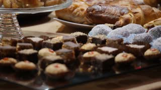A moving shot of several types of small cakes exposed for sale for the consumers...