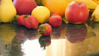 A moving shot showing some fruits on a table and a blender mixing fruits and making a fresh juice