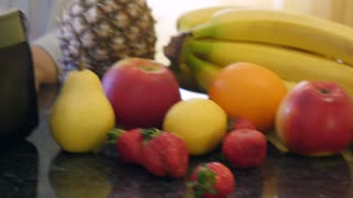 A moving shot showing some fruits on a table and a blender mixing fruits and making a fresh juice...
