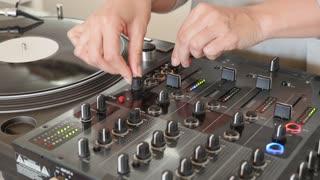 A person mixes music on an audio mixer...