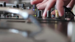 A person mixing music on an audio mixer, the shot moves from the audio mixer to the vinyl...