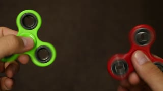 A person playing with two fidget spinners at the same time, isolated on a dark background...
