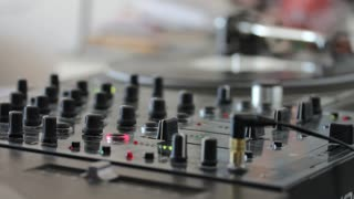 A person practicing mixing music on an audio mixer...