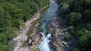 A rafting boat goes down a rapid on a river...