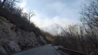 A shot from a car at a mountain road showing a mountain in flames...