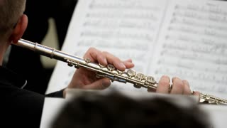 A shot of a musician playing on his flute and looking into music notes in front of him...