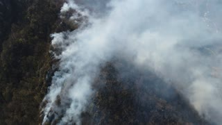 Aerial footage of a flared up woods covered in thick smoke...
