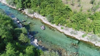 Aerial footage of a group of rafters in a boat going down the river, the camera is following them...