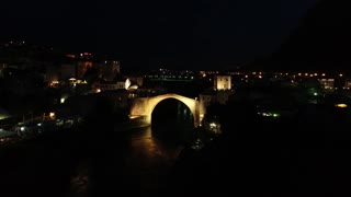 An aerial moving shot showing Mostar and it´s old bridge at night...