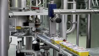 Cheese spread production line at a company, the product is filled and sealed and its heading to the cooling machine