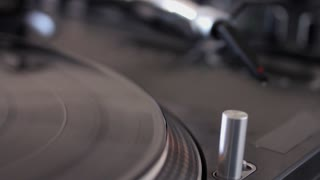 Close up footage of a DJ putting the spherical needle on a vinyl...