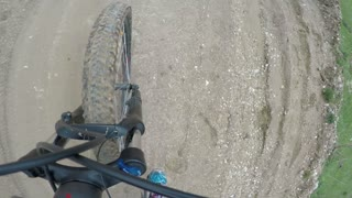 Close up footage of a mountain bikes front wheel and the ground, he is riding downhill...