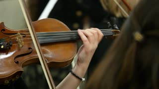 Close up footage of a person playing on an old violin...