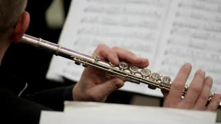 Close up footage of a person playing on his flute