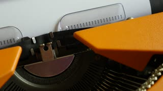 Close up footage of a person writing EPILOGUE on an old typewriter...