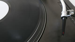 Close up footage of a turning vinyl and a spherical needle on it...