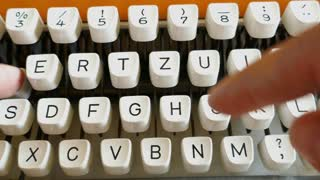 Close up footage of an old typewriter and a person typing on it...