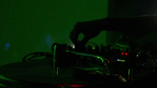 Close up shot of a vinyl on a DJ´s mixer and a DJ mixing music in a club...