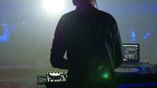 Footage of a DJ mixing music, the shot is taken behind the DJs back...