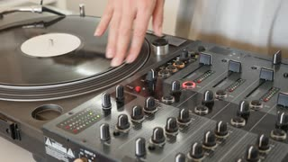 Footage of a DJ scratching on a vinyl and mixing music on an audio mixer...