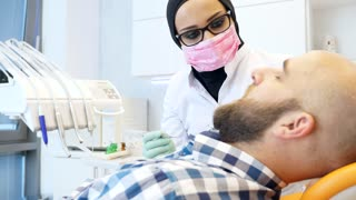 Footage of a female dentist in hijab working on a patients teeth...