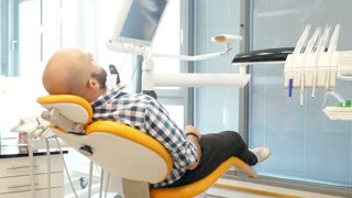 Footage of a male patient sitting in a dentists chair, he turns, smiles into camera and shows a thumb up