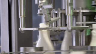 Footage of a milk production line, the bottles are filled with milk and then hermetically sealed...