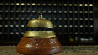Footage of a person ringing on a bell at a hotel reception...