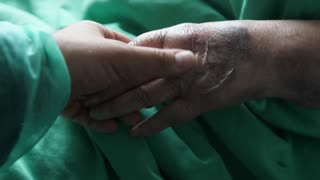 Footage of a person visiting grandma in a hospital and stroking her hand...