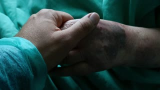 Footage of a person visiting grandmom in a hospital and stroking her hand
