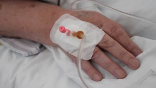 Footage of an old person lying in bed at a hospital with the cannula in the persons hand...