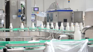 Footage of milk bottles at the production line in a milk company...