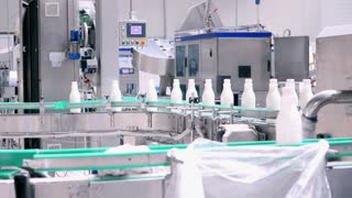 Footage of milk bottles at the production line in a milk company