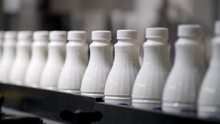 Footage of white plastic milk bottles sorted at the production line and moving forward in a milk company