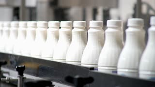 Footage of white plastic milk bottles sorted at the production line and moving forward to be packed
