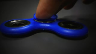Low angle footage of a blue fidget spinner lying on a gray surface and a person spins it...