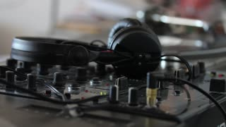 Side shot of an audio mixer and a person takes the headphones and starts to mix music...