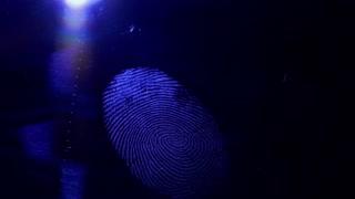 Somebody lighting up a fingerprint left on a dark surface...