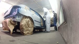 Wide angle footage of a car being painted and varnished in a painting chamber...