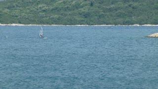 Wide shot of a windsurfer enjoying in windsurfing on a lake